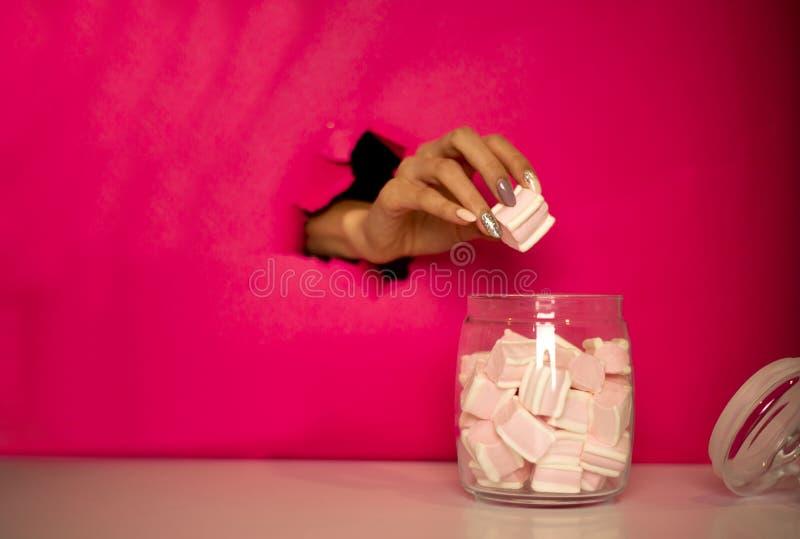 A m?o ? roubo dos marshmallows fotos de stock royalty free