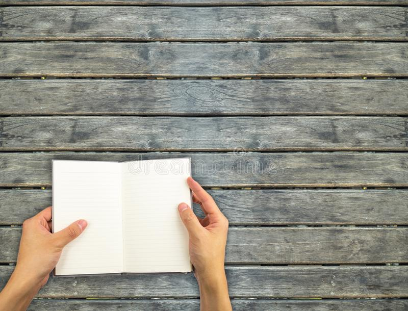 Mão aberta do caderno que guarda sobre a parede de madeira imagens de stock royalty free