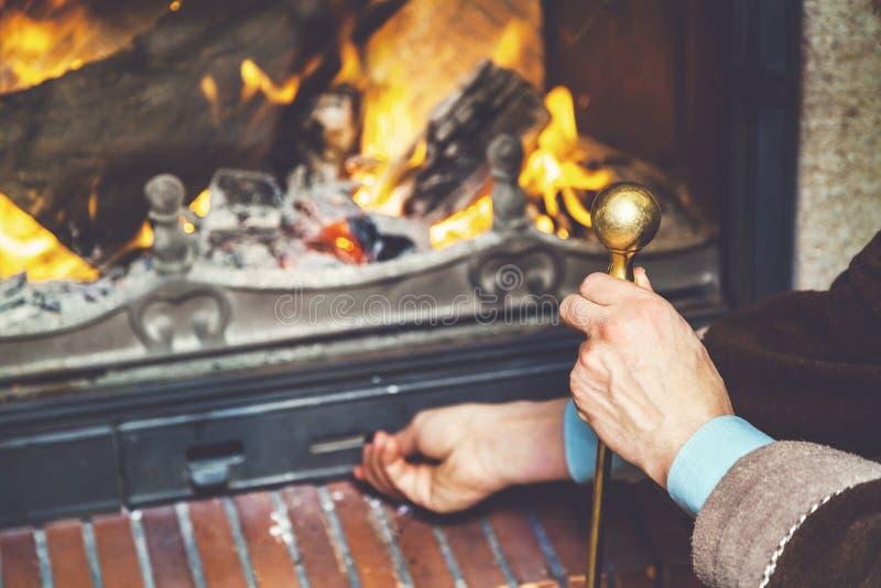 A mão abre o fogo da bandeja da cinza que queimam a lenha fotos de stock royalty free