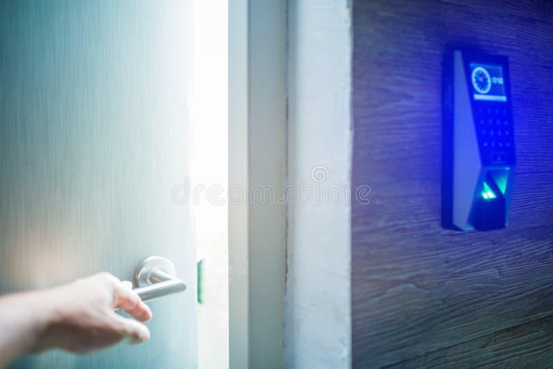 A mão abre a porta com sistema do controle de acesso da varredura do dedo para destravar na sala segura E imagem de stock