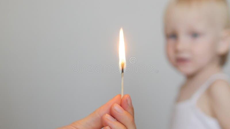 Mão adulta do ` s que guarda um fósforo ardente no retrato do fundo de uma criança, fogo, conceito, close-up, cópia-espaço, branc fotografia de stock royalty free