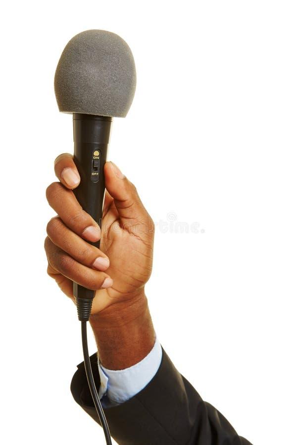 Mão africana que guarda o microfone fotografia de stock