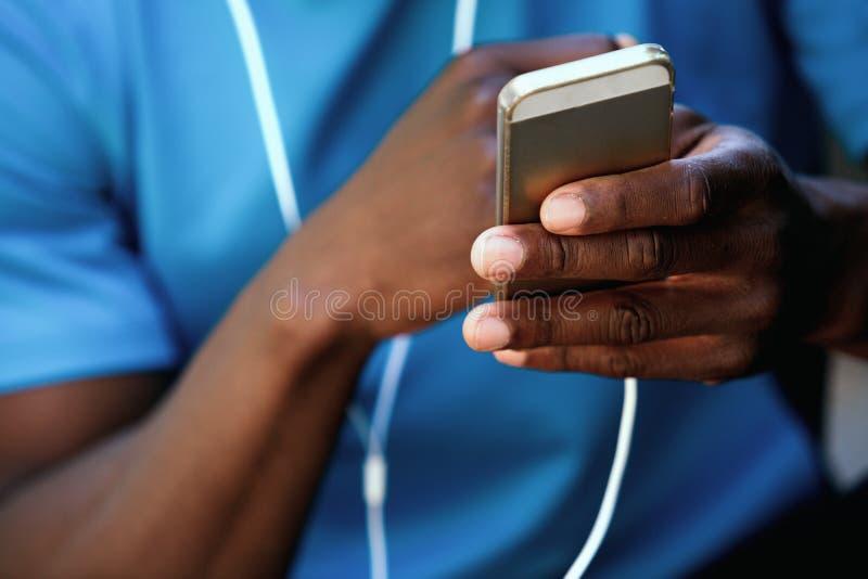 Mão afro-americano do homem que guarda o telefone celular imagens de stock royalty free