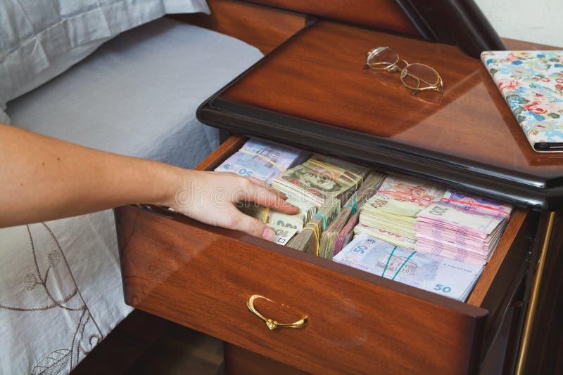 A mão alcança para o dinheiro na tabela de cabeceira fotografia de stock