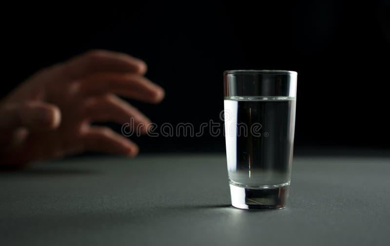 A mão alcança para um vidro da bebida da vodca ou do álcool fotografia de stock