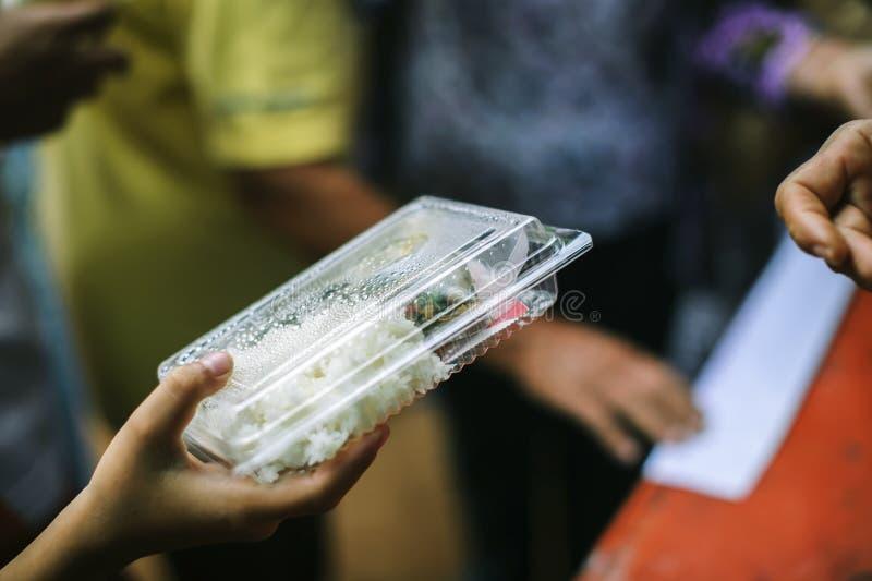 Mão-alimentação ao carente na sociedade: Conceito da alimentação: Os voluntários dão o alimento aos pobres: doar o alimento é aju foto de stock