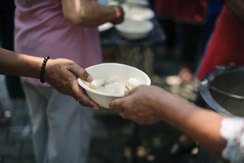 Mão-alimentação ao carente na sociedade: Conceito da alimentação: Os voluntários dão o alimento aos pobres: doar o alimento é aju fotografia de stock royalty free