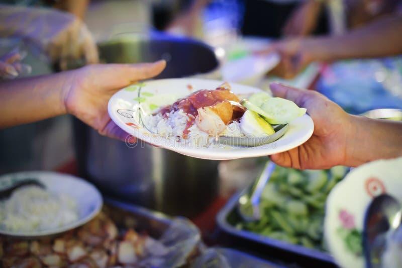 Mão-alimentação ao carente na sociedade: Conceito da alimentação: Os voluntários dão o alimento aos pobres: doar o alimento é aju imagem de stock royalty free