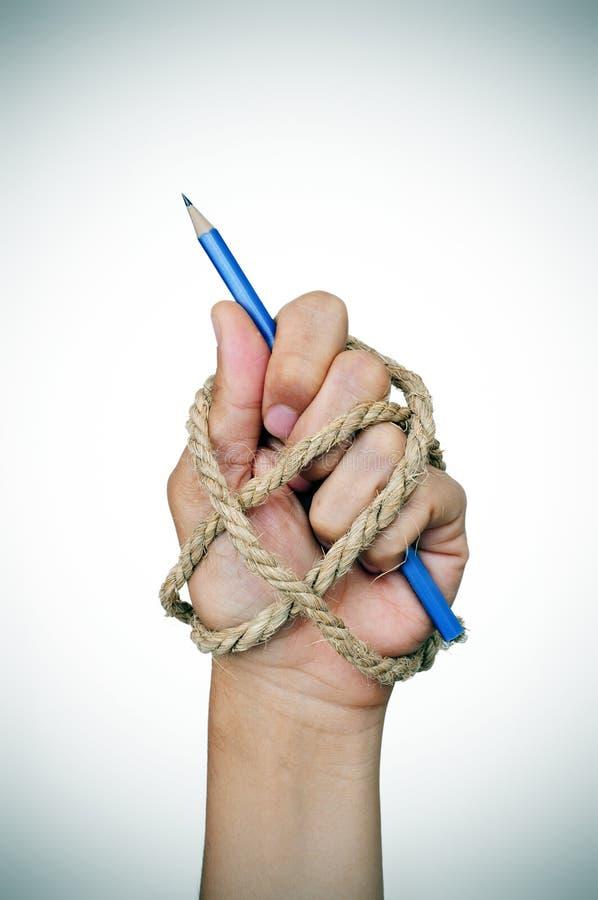 Mão amarrada com a corda que guarda um lápis foto de stock