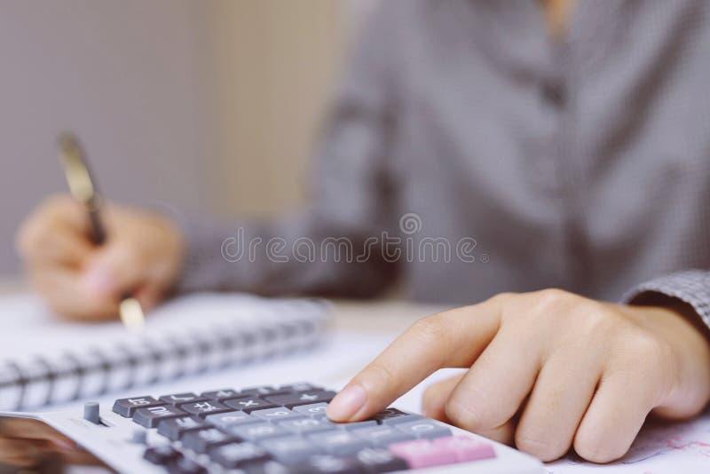 A mão ascendente próxima da jovem mulher está escrevendo em um caderno e está usando a calculadora que conta fazendo as anotações fotos de stock royalty free