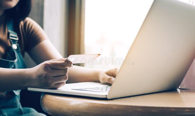 Mão ascendente próxima da mulher que guarda o cartão de crédito e que datilografa o portátil do teclado sobre o conceito em linha foto de stock royalty free