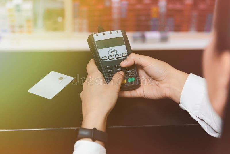 Mão ascendente próxima das mãos da mulher que introduzem o código do pino no cartão de crédito imagens de stock