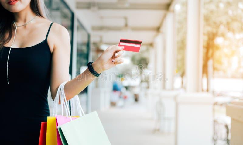 Mão ascendente próxima das mulheres que guardam o cartão e os sacos de compras de crédito no shopping foto de stock royalty free