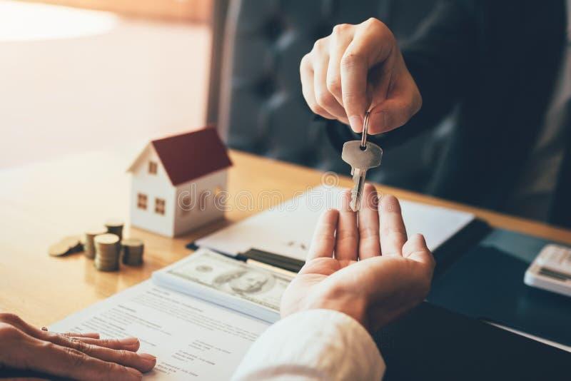 A mão ascendente próxima de agentes da casa está distribuindo chaves aos compradores de casa novos imagem de stock royalty free
