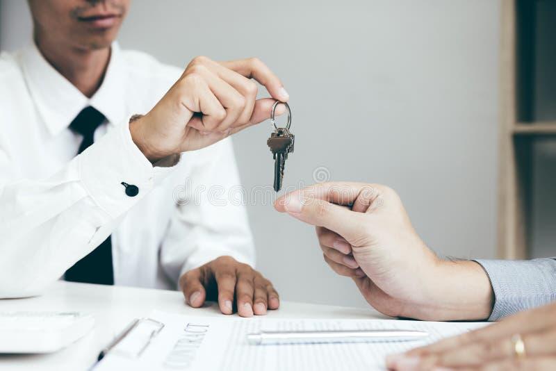 A mão ascendente próxima de agentes da casa está distribuindo chaves aos compradores de casa novos imagens de stock royalty free