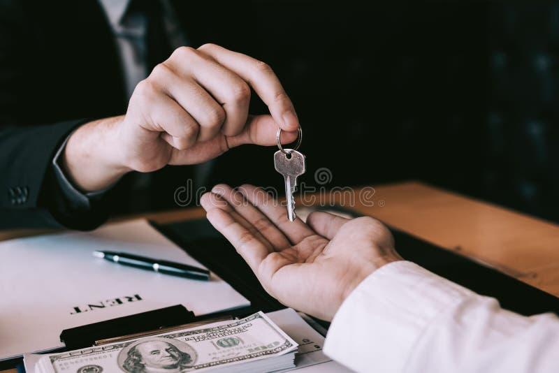 A mão ascendente próxima de agentes da casa está distribuindo chaves aos compradores de casa novos imagem de stock
