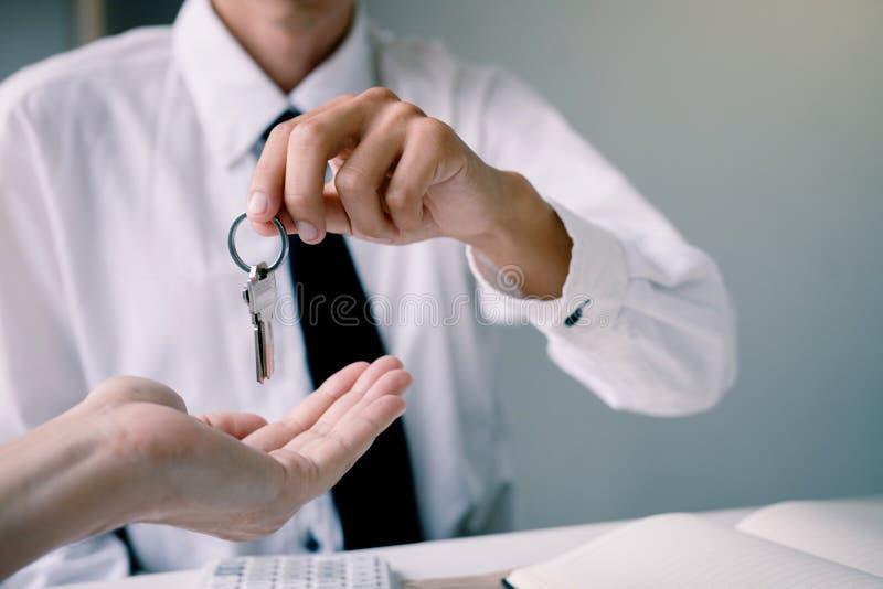 A mão ascendente próxima de agentes da casa está distribuindo chaves aos compradores de casa novos fotografia de stock royalty free