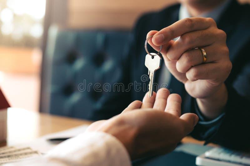 A mão ascendente próxima de agentes da casa está distribuindo chaves aos compradores de casa novos fotografia de stock
