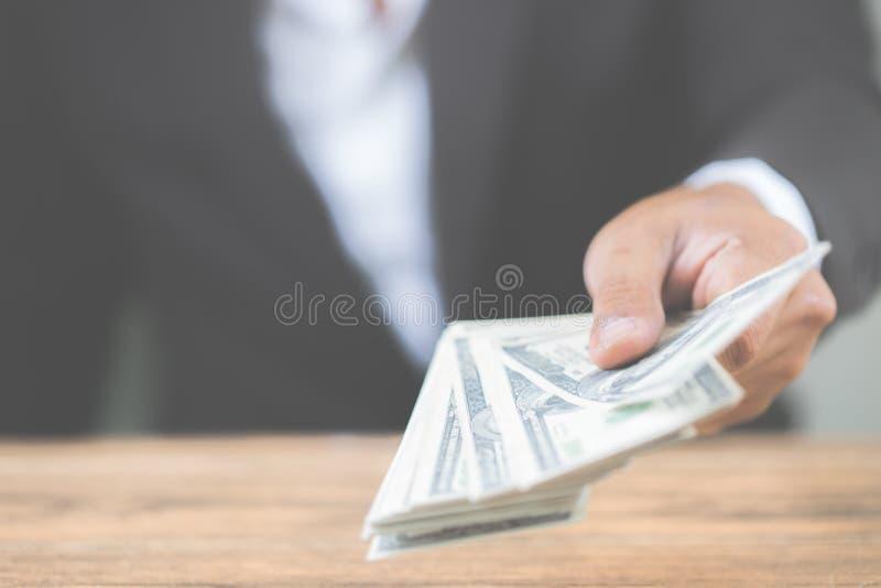 Mão ascendente próxima do homem de negócios que guarda notas de dólar do dinheiro na tabela de madeira Usando-se como o conceito  fotografia de stock