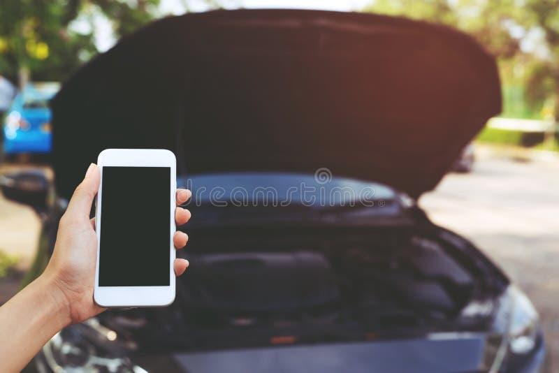 Mão ascendente próxima do homem dos povos usando um telefonema esperto móvel um mecânico de carro imagem de stock