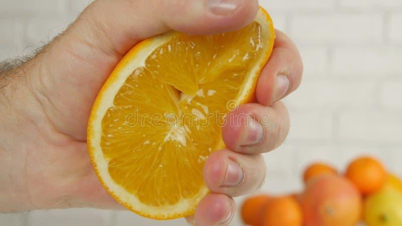 Mão ascendente próxima do homem que espreme um fruto alaranjado doce e suculento imagens de stock