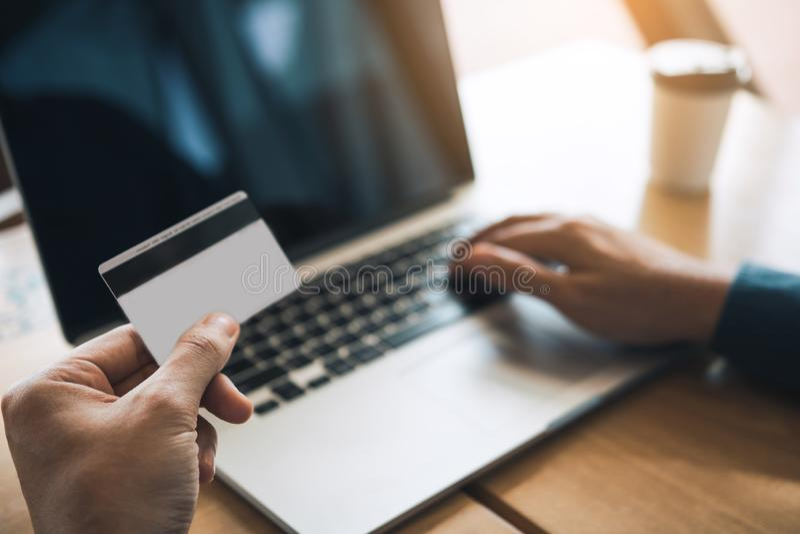 Mão ascendente próxima do homem que guarda o cartão de crédito e que datilografa o teclado do portátil com conceito em linha de c fotografia de stock royalty free