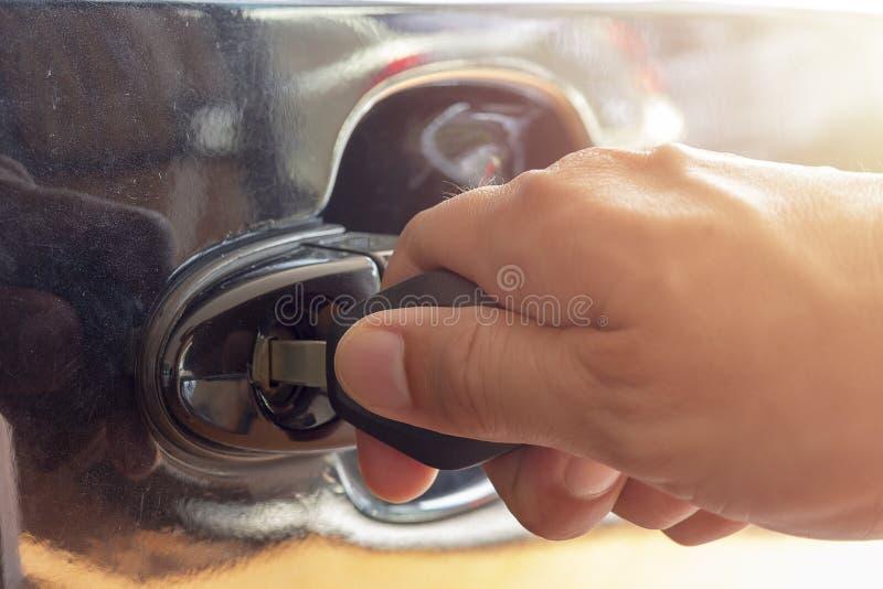 Mão ascendente próxima do homem que introduz uma chave na fechadura da porta um carro foto de stock royalty free