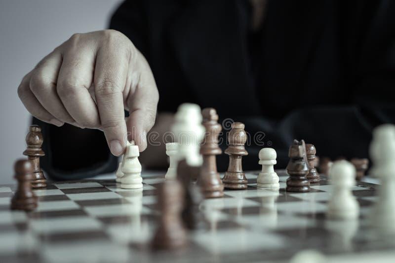 Mão ascendente próxima do tiro da mulher de negócio que joga a placa de xadrez para ganhar matando o rei da competição oponente d foto de stock royalty free