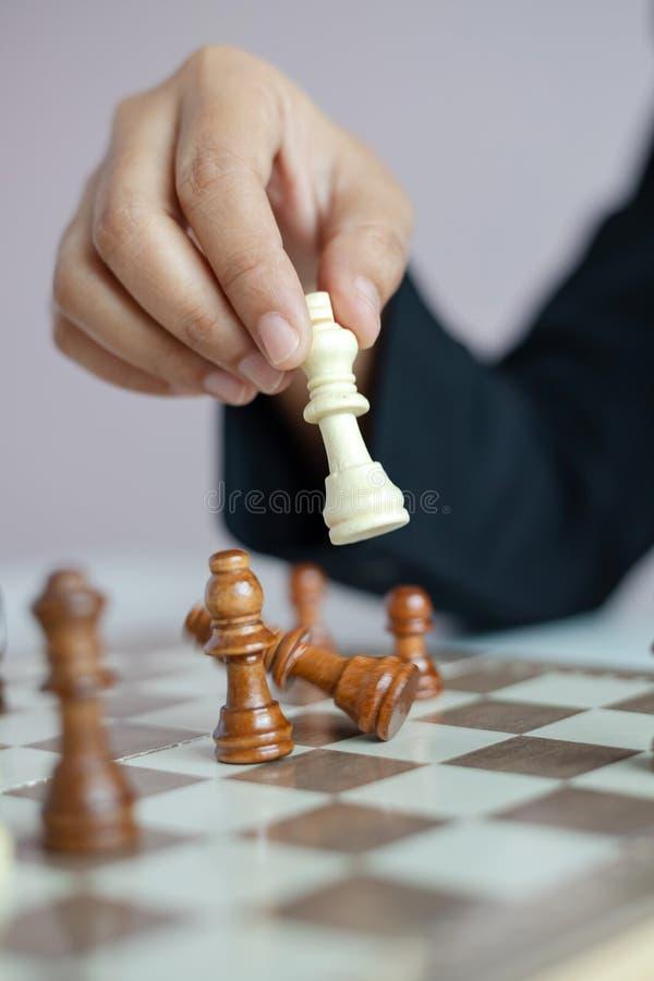 Mão ascendente próxima do tiro da mulher de negócio que joga a placa de xadrez para ganhar matando o rei da competição oponente d fotos de stock royalty free