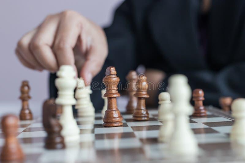 Mão ascendente próxima do tiro da mulher de negócio que joga a placa de xadrez para ganhar matando o rei da competição oponente d fotos de stock