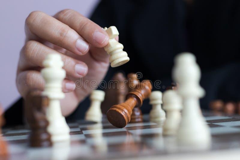 Mão ascendente próxima do tiro da mulher de negócio que joga a placa de xadrez para ganhar matando o rei da competição oponente d imagem de stock royalty free