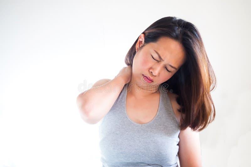 Mão asiática adulta média do uso da mulher que faz massagens o ombro Sintomas o foto de stock royalty free