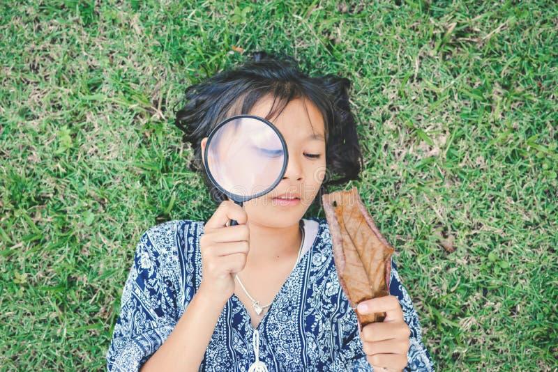 Mão asiática da menina que guarda a lupa no jardim imagens de stock