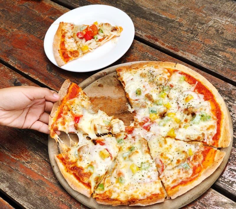 Mão asiática da mulher que escolhe a pizza em uma bandeja dividida em partes em uma tabela de madeira imagens de stock royalty free