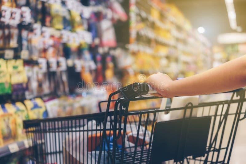 Mão asiática do ` s da mulher com supermercado, trole e th de muitos objetos fotos de stock royalty free