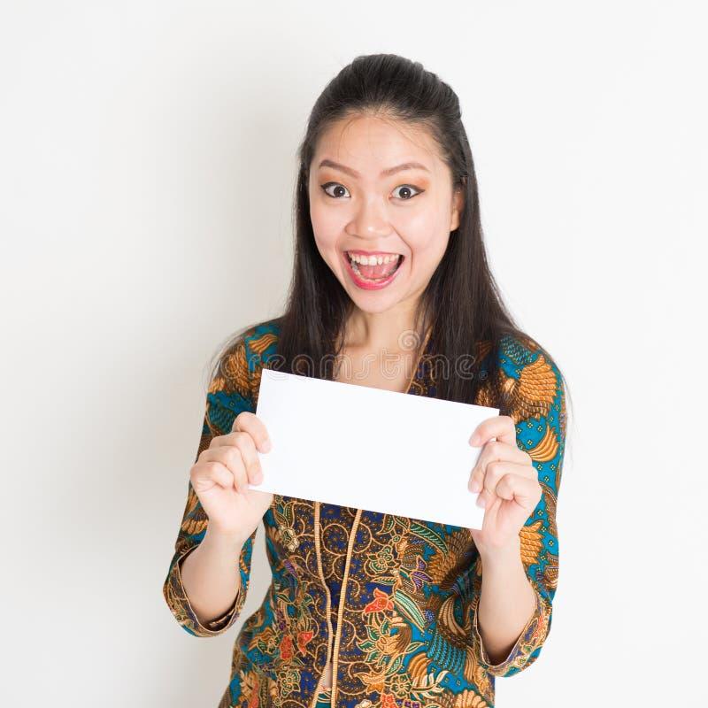 Mão asiática do sudeste da mulher que guarda o cartão do Livro Branco fotografia de stock royalty free