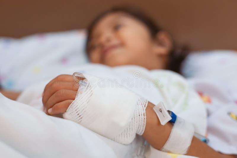 A mão asiática doente da menina da criança pequena que tem a atadura intravenosa salina do gotejamento do iv está dormindo na cam fotografia de stock royalty free