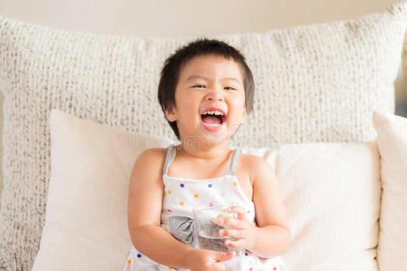 Mão asiática pequena feliz da menina que guarda o vidro de água potável foto de stock