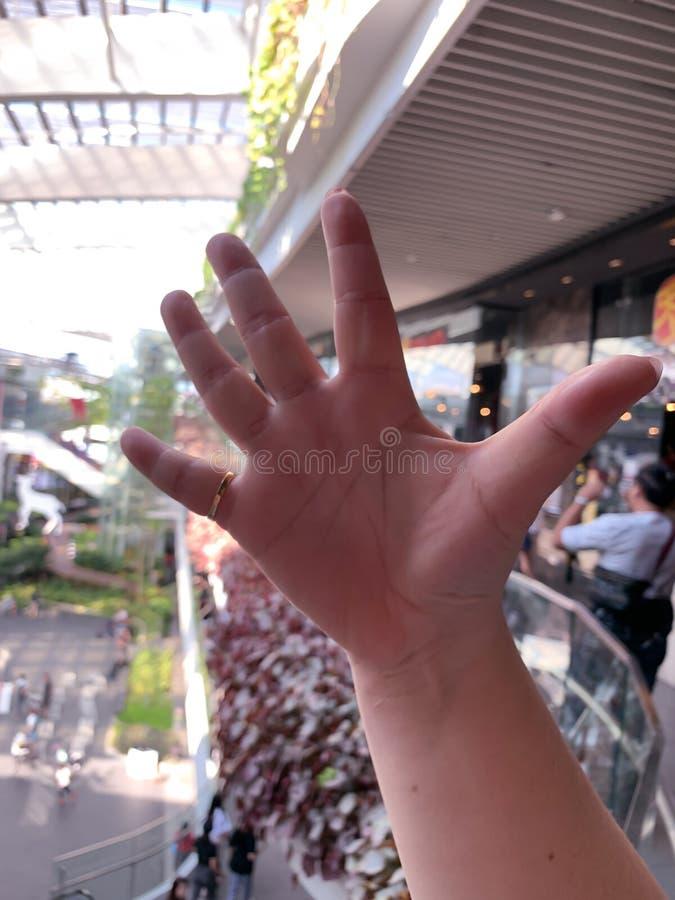 A mão assina dentro o fundo da alameda imagens de stock