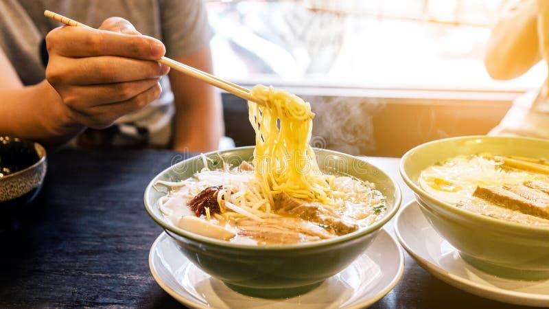 Mão beliscando macarrão com vapor em Ramen Broth com Pasta de Spicy Bean Miso Ramen com Chashu Pork, Scallion, Sprout, Milho foto de stock royalty free