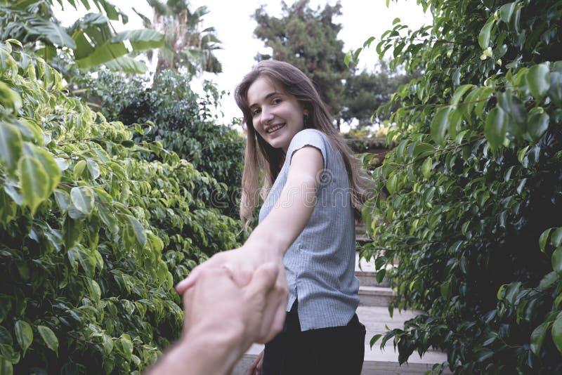 Mão bonita da terra arrendada da mulher de seu noivo no parque fotografia de stock