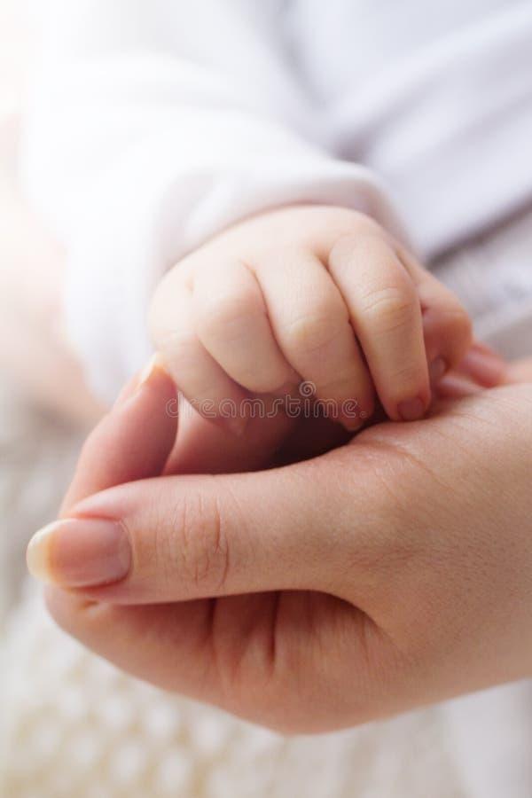 Mão bonito pequena do bebê na mão das mães closeup Conceito de matern fotografia de stock royalty free