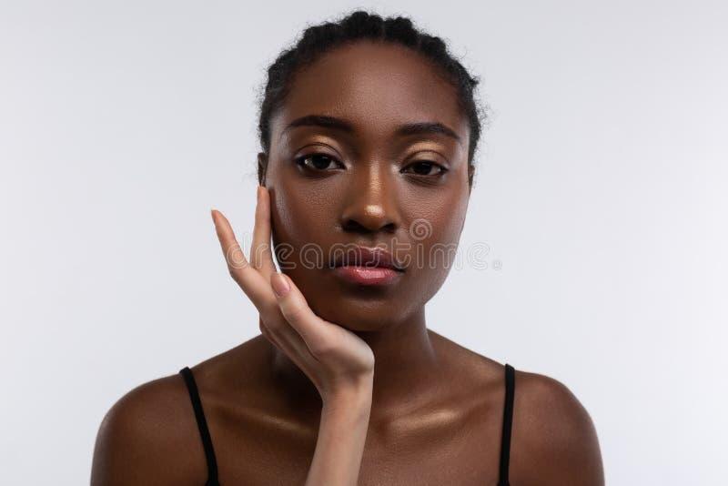 M?o branca que toca na cara da mulher bonita de pele escura imagens de stock royalty free