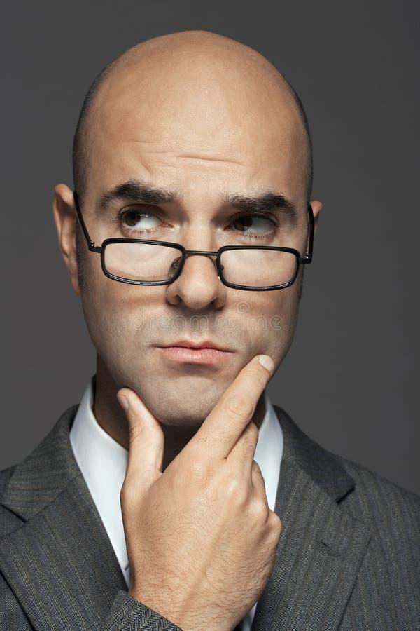 Mão calva de Wearing Glasses With do homem de negócios em Chin foto de stock