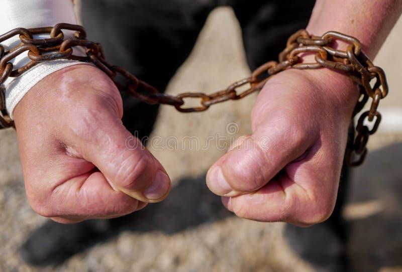 Mão caucasiano do homem em correntes oxidadas fotografia de stock