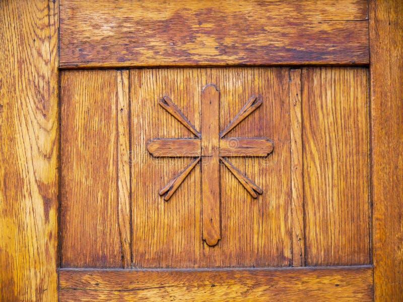 A mão cinzelou a cruz na porta de madeira do carvalho da igreja Católica imagens de stock royalty free