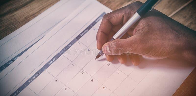A mão colhida da marcação do homem de negócios data no calendário imagens de stock royalty free