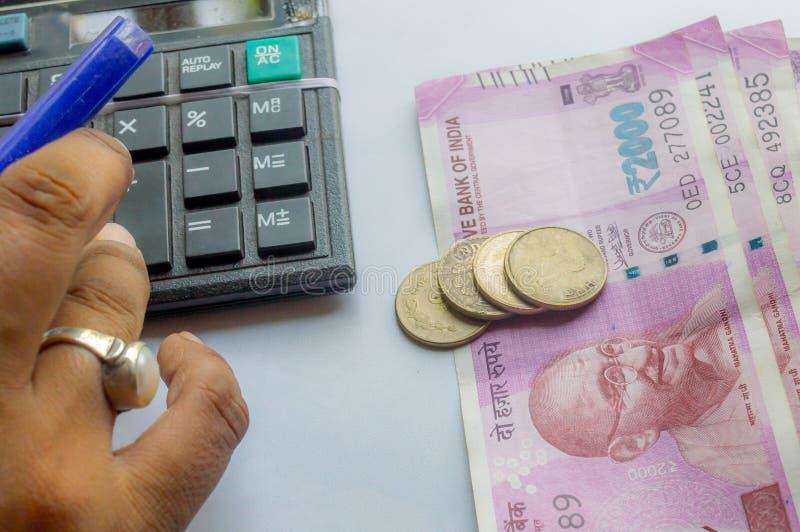 Mão colhida de uma conta corrente da mulher com calculadora e guardar uma pena As notas e as moedas indianas da moeda estão no la foto de stock