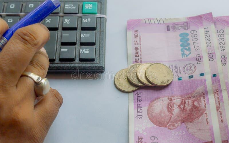 Mão colhida de uma conta corrente da mulher com calculadora e guardar uma pena As notas e as moedas indianas da moeda estão no la imagem de stock