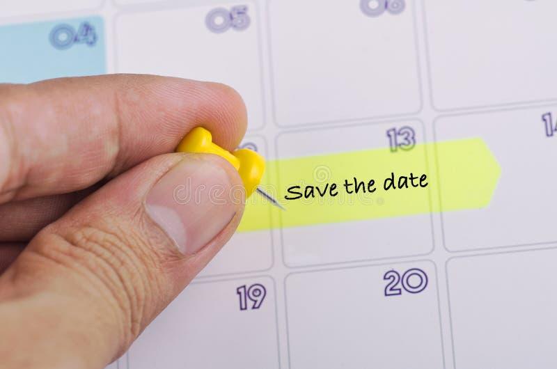 Mão colhida e papel pegajoso amarelo com palavra SALVO A DATA no calendário fotos de stock royalty free
